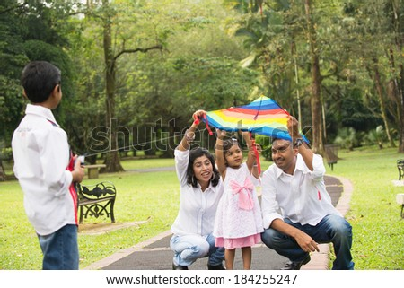 indian family playing kite in the outdoor park - stock photo