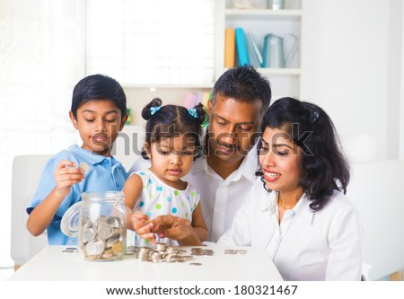 indian family teaching children on savings and financial planning  - stock photo