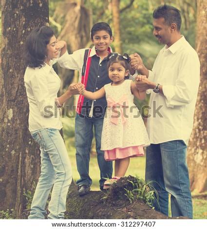indian family teaching children to climb - stock photo