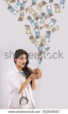 indian female doctor holding piggy bank or money box made up of clay and indian currency falling from sky, indian currency raining, isolated on gray, indian doctor and money or rupees - stock photo