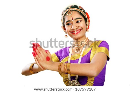 Indian female performing Bharathanatyam doing the action of giving respect  in violet color costumes  - stock photo