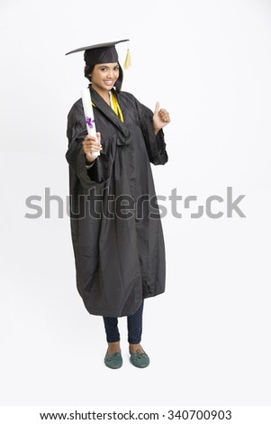 Indian girl college graduate wearing cap and gown holding diploma and showing thumbs up. - stock photo