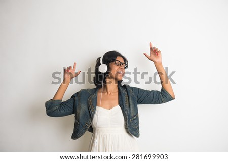 Indian girl dances while listening to her music - stock photo