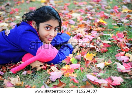 Indian girl showing expression in autumn park - stock photo