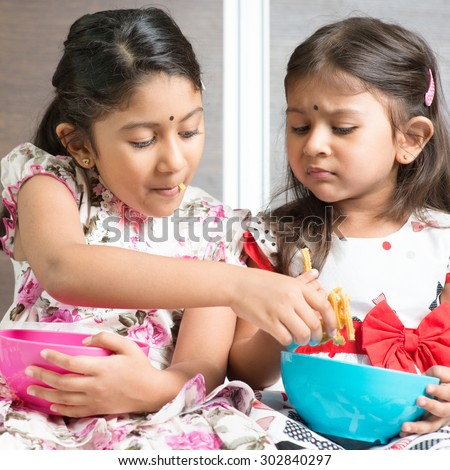 Indian girls sharing food, traditional snack murukku with each other. Asian sibling or children living lifestyle at home. - stock photo
