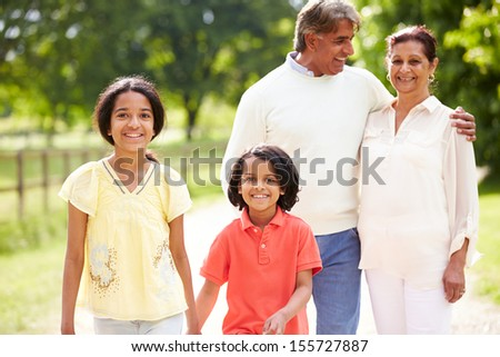 Indian Grandparents And Grandchildren Walking In Countryside - stock photo