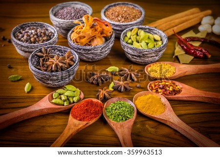 Indian herbs and spices beautifully arranged in wooden spoons and stone bowls arranged over wooden textured table - stock photo