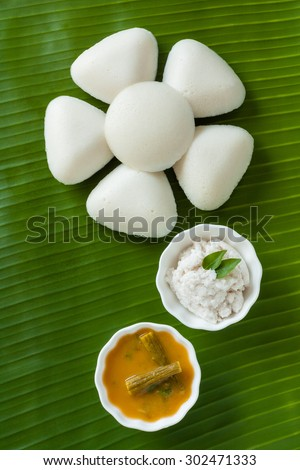 Indian idly served as a flower - Fresh steamed Indian Idly (Idli / rice cake) arranged decoratively as a flower on traditional banana leaf. Served with coconut chutney and sambar. Natural light used. - stock photo
