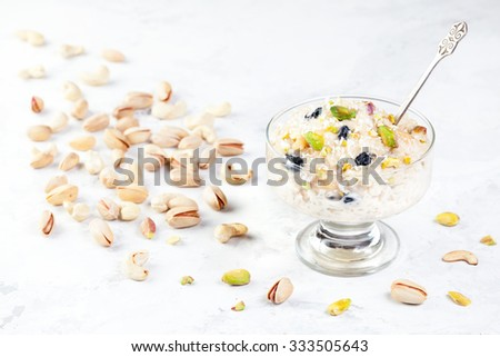 Indian Kheer sweet dessert from rice, nuts and spices in ice cream bowl on white marble table - stock photo