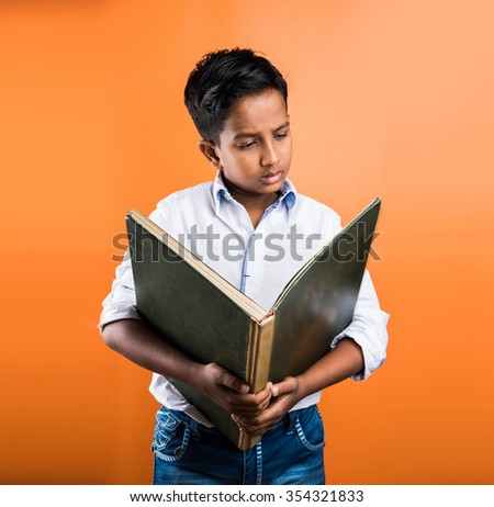 Indian kid enjoying reading book, asian kid reading book, african kid reading book, indian kid studying, indian kid holding book, portrait, indian kid standing with book, geography book, orange back  - stock photo