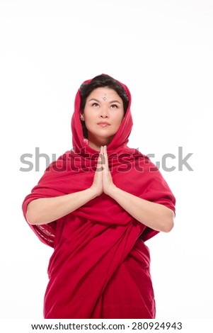 Indian lady dressed in traditional red-coloured sari with her hands clasped seems that she is communicating with God. - stock photo
