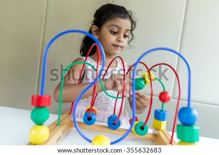 Indian little girl play with the wried loop of wooden bead - stock photo