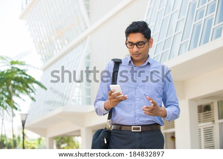 indian male business man reading or using smart phone - stock photo