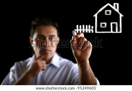 Indian male businessman with marker in fictional house writting something - stock photo