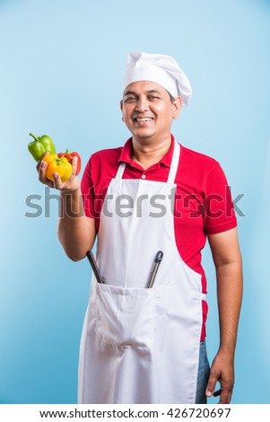 indian Male chef showing capsicum , asian male cook chef and colorful capsicum, isolated over blue background - stock photo