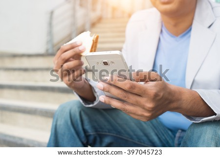 indian male eating a quick sandwich outdoor in casual