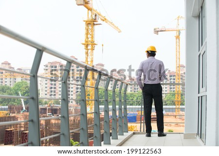 indian male engineer inspecting site with construction background - stock photo