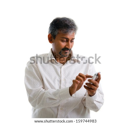 Indian male using mobile phone to online / texting / sms , isolated on white background - stock photo