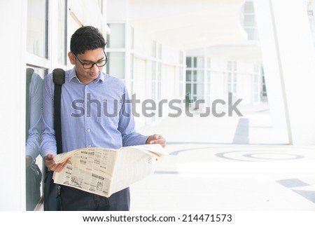 Indian man checking on new office to let, holding newspaper and calling on phone. - stock photo