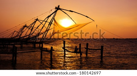 Indian Man Fishing Under The Great Chinese Nets at Cochin, Kerela, India  - stock photo