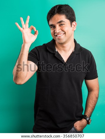 indian man showing best sign, indian man and success, asian man and best sign, isolated on green background - stock photo