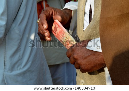 Indian man that counts the banknotes rupee - stock photo