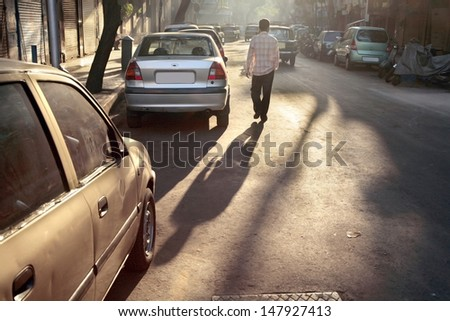 Indian man walking in the middle of a street - stock photo