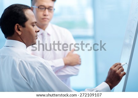Indian manager drawing something on the white board - stock photo