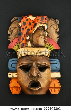 Indian Mayan Aztec wooden carved painted mask with roaring jaguar and human faces isolated on black paper background - stock photo