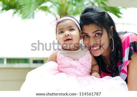 Indian mother and baby girl at outdoor home garden - stock photo