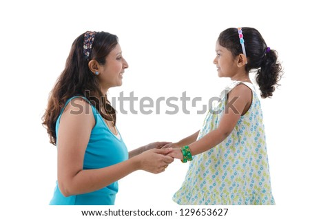 indian mother and daugther staring at each other - stock photo