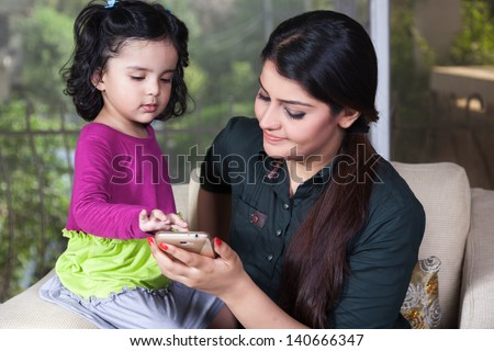 Indian mother and her daughter using smart phone, - stock photo