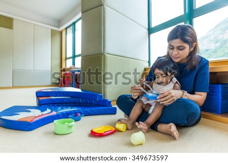 Indian mother play with her daughter at home - stock photo