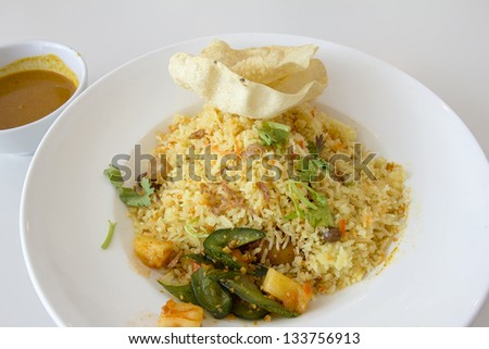 Indian Nasi Biryani Rice Dish with Curry Sauce Pickled Vegetable and Crackers Local Dish - stock photo