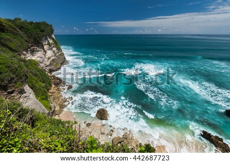 Indian ocean's coast with breaking waves and blue sky with some clouds. Bali, Indonesia - stock photo