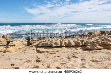 Indian Ocean waves rolling in to the limestone covered beach at Penguin Island in Rockingham, Western Australia/Limestone Beach/Penguin Island, Rockingham, Western Australia - stock photo