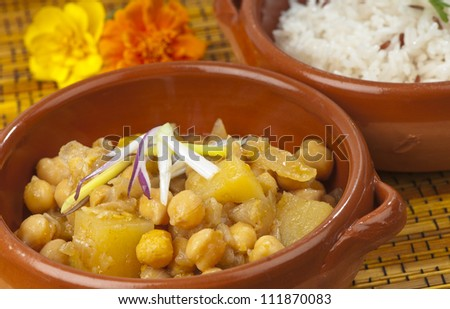 Indian or Thai chickpea and potato curry in an earthenware dish with a separate dish of white basmati rice.  On a bamboo mat . Garnished with red onions and marigold flowers. - stock photo