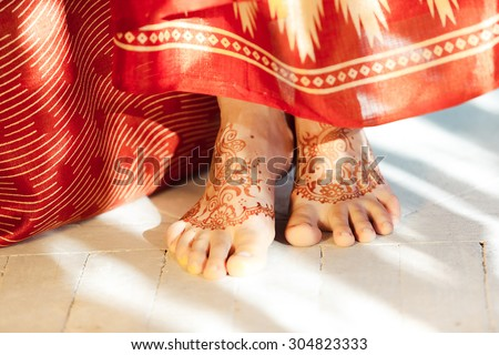 Indian picture on woman feet, mehendi tradition decoration, resistant design by special paint, brown henna.  Indian red dress on white background - stock photo