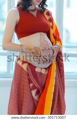 Indian picture on woman hands and pregnant belly with henna tattoo  on white room background    - stock photo