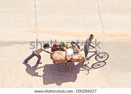 Indian rickshaw loaded with cargo, way to the bazaar - stock photo