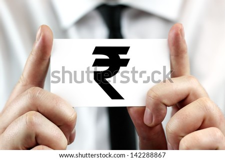 Indian Rupee symbol. Businessman in white shirt with a black tie, shows business card - stock photo