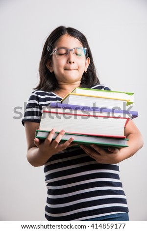 indian small girl holding a pile of books, asian little girl holding pile of books in both hands, feeling heavy, funny expressions - stock photo