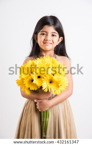 indian small girl holding bouquet of yellow gerbera flowers, isolated over white background, indian girl and flowers, asian girl with flowers - stock photo