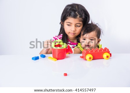 indian small girl or asian girl child playing with colorful blocks over white background, cute little indian girl constructing house with blocks, cute indian girl playing with toys - stock photo