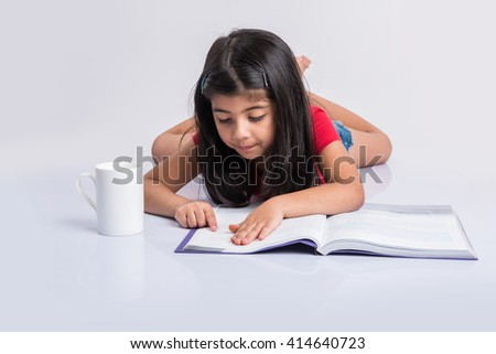 indian small girl reading book, asian girl child reading book over white background, cute 5 year old indian small girl reading book with milk mug - stock photo