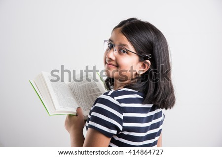 indian small girl with eye glasses standing and reading a book, asian little girl holding a book and reading over white background, cute indian girl wearing spectacles and reading book while standing - stock photo