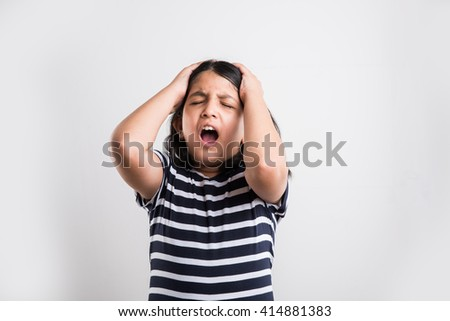 indian small girl with headache, asian cute girl having headache, indian small girl stressed and sad because of head ache - stock photo