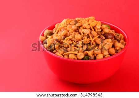 Indian Snacks : Mixture (roasted nuts with salt pepper masala, pulses, channa masala dal, green peas) in red bowl on red background   - stock photo