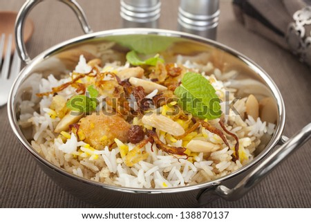 Indian special occasion dish, chicken biryani is garnished with crisp fried onions, sultanas, almonds and mint. - stock photo