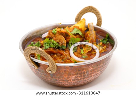 Indian style meat dish or mutton curry in a copper brass bowl isolated on white background. - stock photo